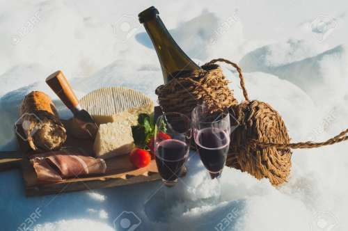 161100125-romantic-picnic-with-lambrusco-cheese-baguette-and-ham-on-snow-traditional-italian-food-and-drink-ou
